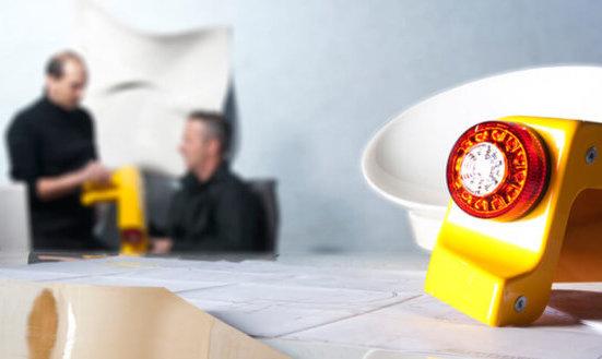 Plastikteil mit roter Rückleuchte während zwei Männer im Hintergrund arbeiten