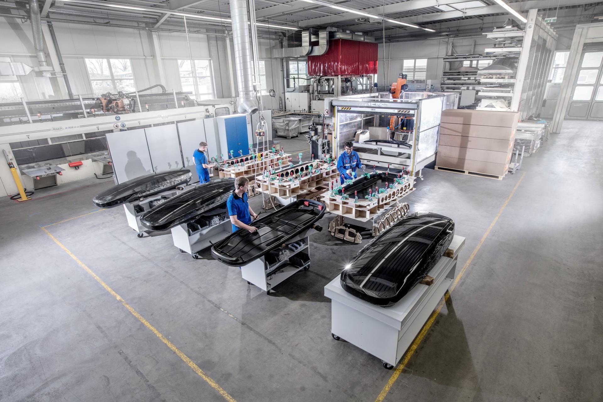 Mitarbeiter stellen Dachboxen in einer swissplast Fabrik her