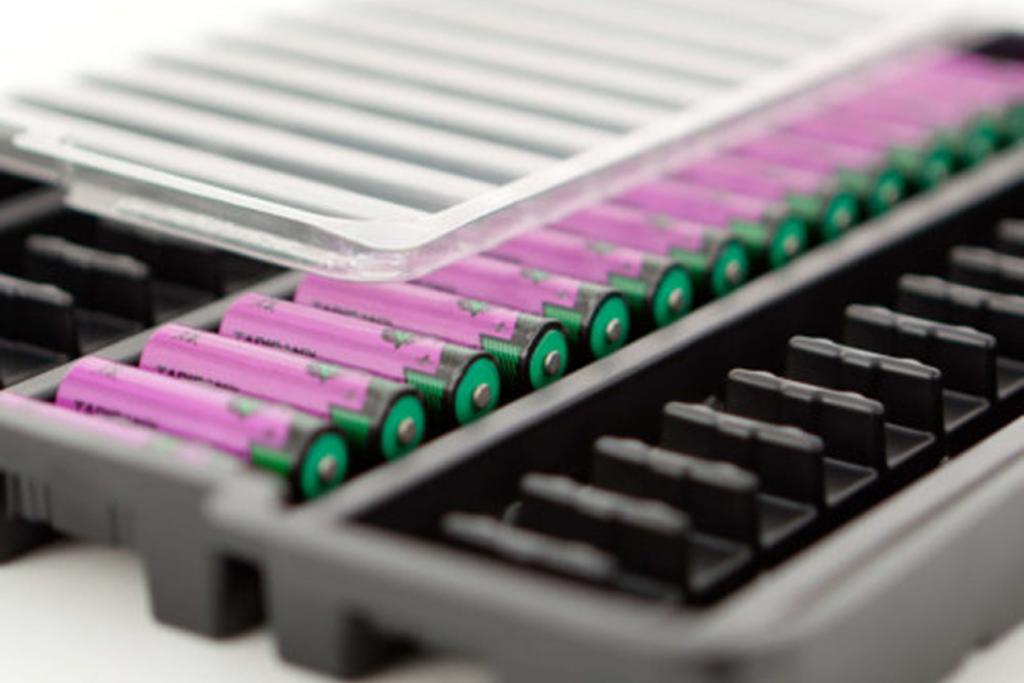 schwarze Werkstückträger mit verpackten Batterien