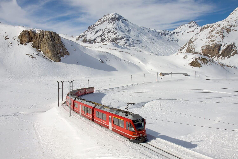 Elektrische Bahn fährt durch Schweizer Schneelandschaft mit Bergen im Hintergrund