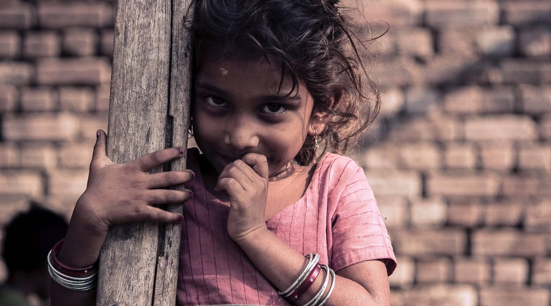 Mädchen in einem rosa Tshirt lehnt an einem Holzbalken und lächelt