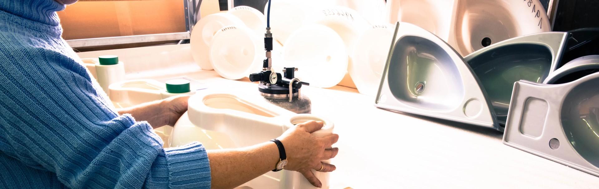 Mann mit blauem Pullover bearbeitet ein swissplast Kunststoffteil