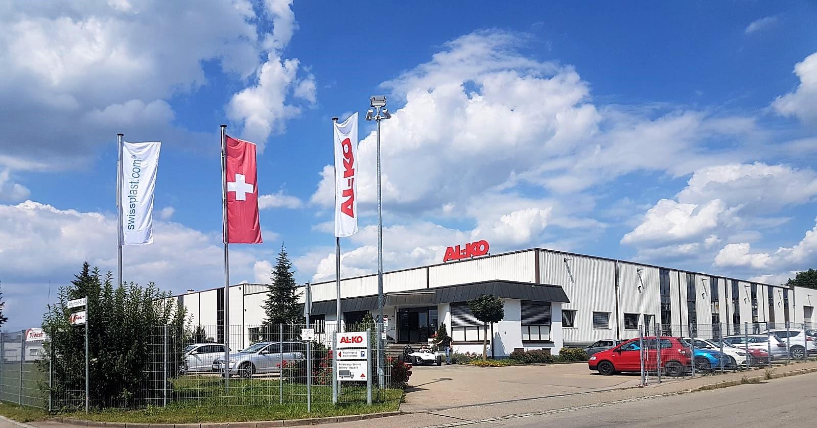 Das AL-KO Gebäude an einem schönen Tag mit swissplast Flagge, Schweizer Flagge und AL-KO Flagge