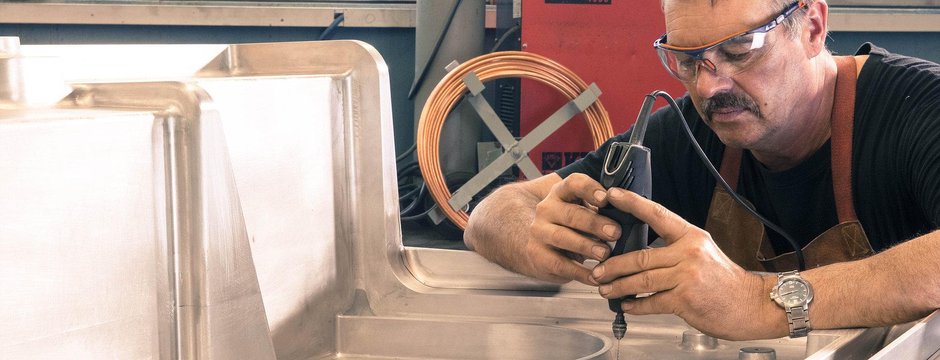 Mitarbeiter von swissplast bohrt an einem Metallteil