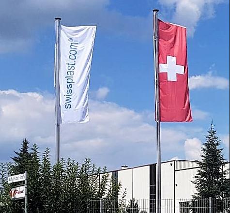 die weisse swissplast Flagge und die Schweizer Nationalflagge wehen im WInd