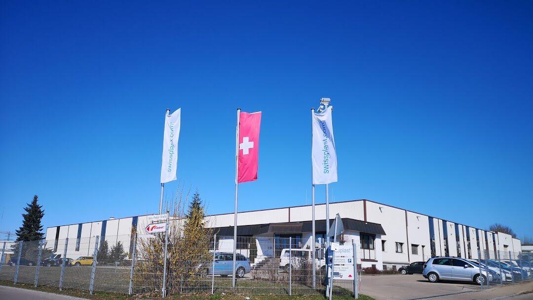 Zwei swissplast Flaggen und eine Schweizer Flagge stehen vor dem swissplast Firmengebäude